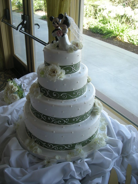Four tier buttercream wedding cake with Minnie and Mickey Mouse toppers