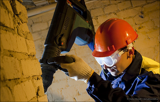 Workman hold perforator and drilling brick wall