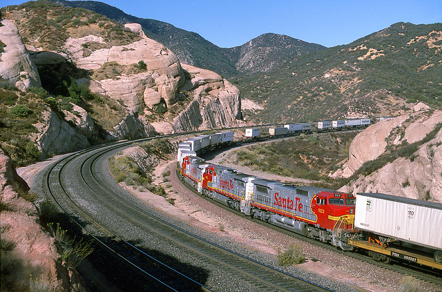 A trio of Warbonnet Santa Fe Dash 8s are very unusual mid-train helpers for an eastbound intermodal climbing Cajon Pass at Sullivans Curve