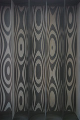 window treatment(0.0), decor(0.0), textile(0.0), brown(0.0), curtain(0.0), window covering(0.0), interior design(0.0), circle(0.0), pattern(1.0), line(1.0), design(1.0), wallpaper(1.0), black(1.0), modern art(1.0),