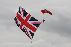 wing(0.0), flag of the united states(0.0), sport kite(0.0), toy(0.0), kite sports(1.0), sports(1.0), red(1.0), windsports(1.0), wind(1.0), flag(1.0),