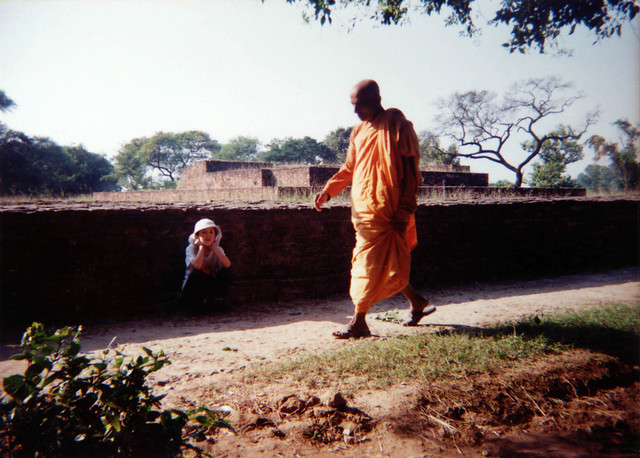A monk dressed in orange robes walks by a young American boy visiting the location of Buddha's meditation garden at Shravasti, where Buddha spent many rainy seasons, bricks mark the old layout of the space, India