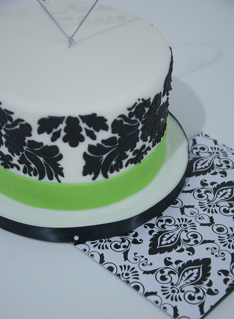 A small white fondant wedding cake with a black damask print and an apple