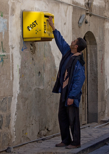 Man putting a letter in a mailbox - Sanaa - Yemen