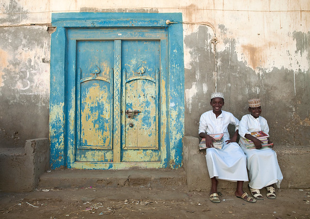 Mirbat boys sitting on a bench with school books, Dhofar, Oman