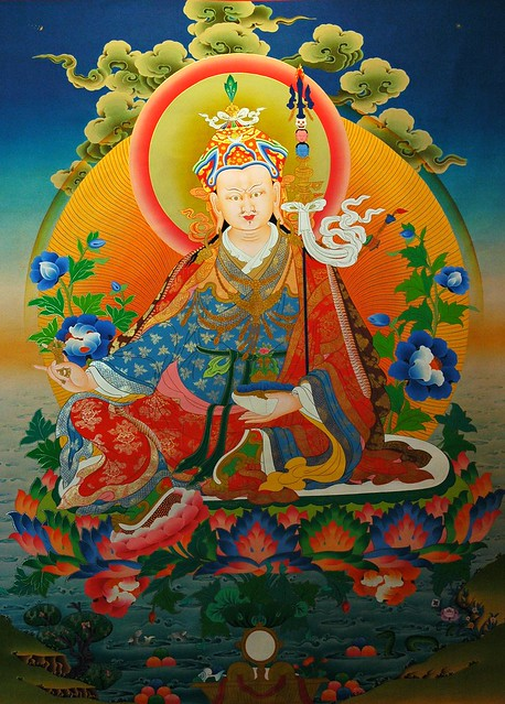 Painting of Padmasambhava, Guru Rinpoche seated on a moon lotus, with vajra, skullcup, khatvanga staff, blue lotuses, vulture feather hat, 7 robes,Tibetan Thangka, 8th Century Saint, from a shop in Bodha, Kathmandu, Nepal