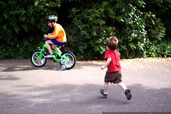little brother chasing big brother on his bicycle   …