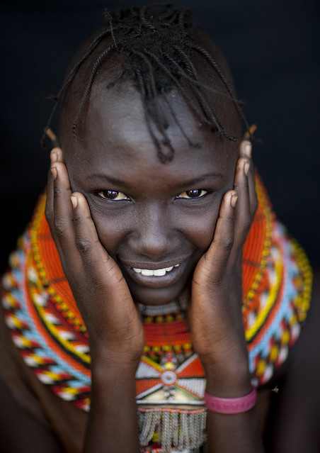 Turkana tribe girl with ahnds on cheeks - Kenya