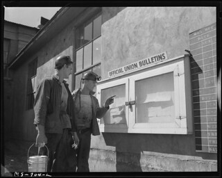 J. M. Hawkins, Former Pharmacist's Mate in the U.S. Navy and William Smith, Former Marine, Read Notice on the Bulletin Board at the Mine