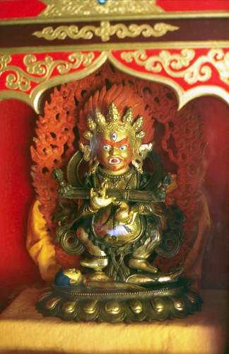 Statue of Shri Mahakala, protector, orange hair, crown of skulls, holding chopper and skull, ritual stick, burning flames of wisdom, Tibetan Buddhism, Sakya school monastery, Pharping, Nepal in 1990 by Wonderlane