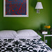 Punchy green bedroom: Black + white bedspread + colorful modern art, by Sheila Bridges