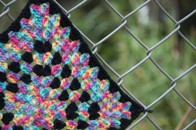 Yarn bomb - granny square on fence