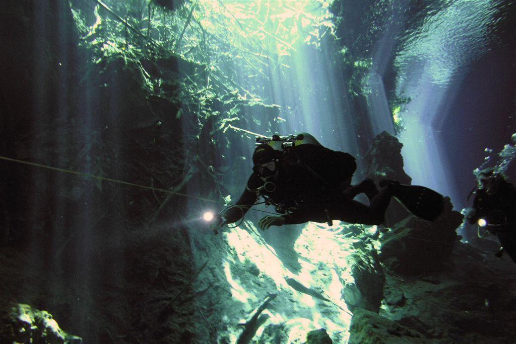 セノーテを懐中電灯を照らしながら探検する人