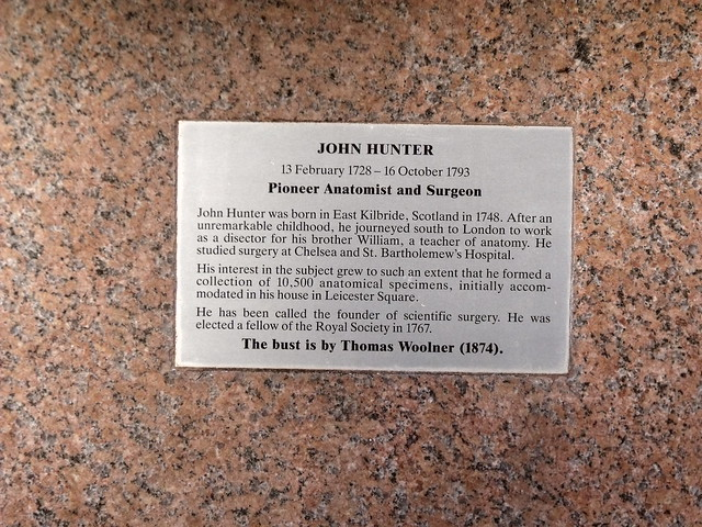 John Hunter brass plaque - John Hunter, 13 February 1728 - 16 October 1793, Pioneer Anatomist and Surgeon.    John Hunter was born in East Kilbride, Scotland in 1728. After an unremarkable childhood, he journeyed south to London to work as a disector {sic} for his brother William, a teacher of anatomy. He studied surgery at Chelsea and St. Bartholemew's {sic} Hospital.    His interest in the subject grew to such an extent that he formed a collection of 10,500 anatomical specimens, initially accommodated in his house in Le