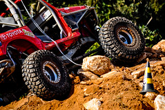 racing(0.0), sports(0.0), endurocross(0.0), dirt track racing(0.0), auto racing(1.0), automobile(1.0), tire(1.0), soil(1.0), wheel(1.0), vehicle(1.0), off road racing(1.0), motorsport(1.0), off-roading(1.0), monster truck(1.0), off-road vehicle(1.0), all-terrain vehicle(1.0),