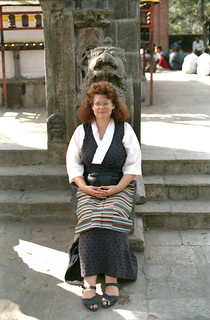 Linda Lane wearing a gray checked Tibetan Chuba, white 3/4 length blouse, and traditional striped apron, seated under a Vajra Guruda statue, courtyard, Swayambunath, Nepal in 1993