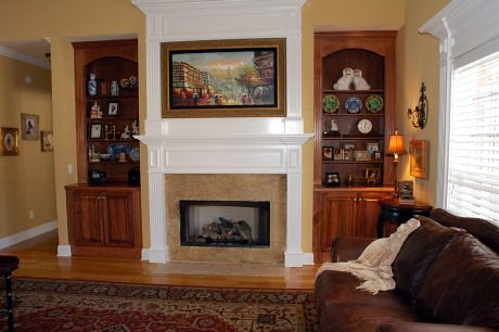 Located behind the picture, revealed at the push of a button is the TV.  With custom built-in cabinets on either side of the fireplace.
