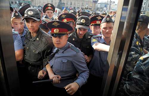 Russian policemen push off journalists during an unauthorized demonstration against politics of Kremlin in central Moscow on July 31, 2009.