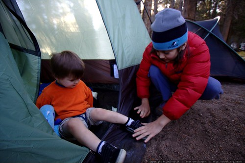 olivia helps her cousin put on his shoes at the tent door    MG 3853