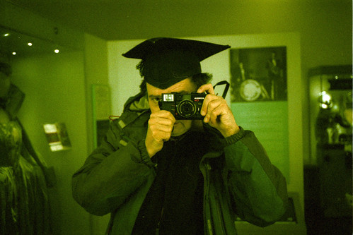 reflected self-portrait with Konica C35 camera and mortar board by pho-Tony