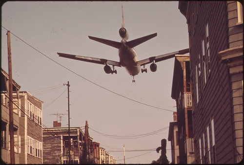Near Logan Airport - Airplane Coming in for a Landing Over Neptune Road Homes by The U.S. National Archives