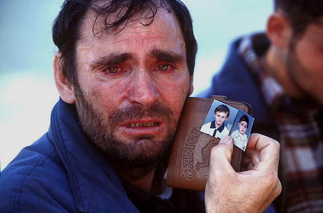 Kosovo, Albanian man, Mustafa Xaja, from the town of Mitrovica in Kosovo shows pictures of his two children he fears to have been killed by Serbs during the war in Kosovo, 1999, by Peter Turnley