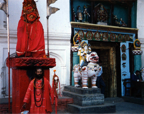 Sadhu in red, under a red shrine, near a store, with Buddhist and Hindu items for sale, Kathmandu, Nepal, 1990, photo by Steve D. by Wonderlane