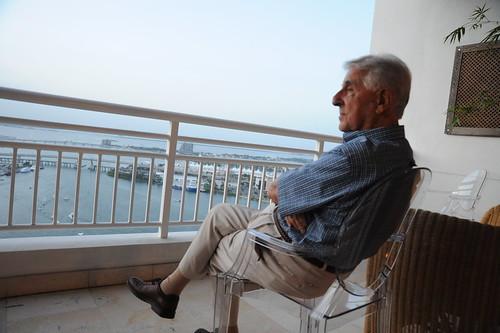 An older man sitting on a balcony.