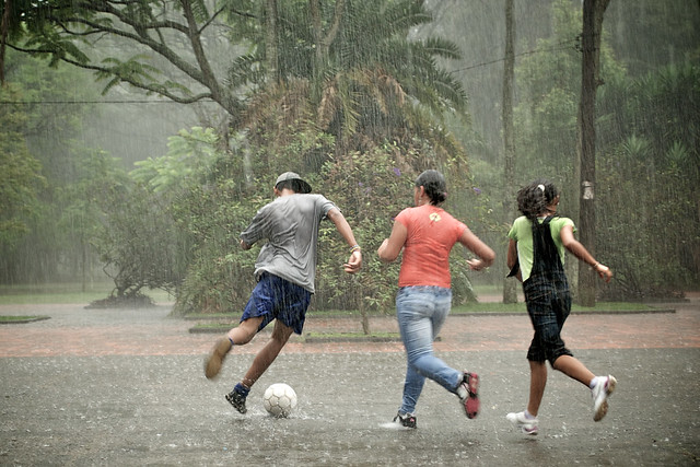 Teenagers playing football in the rain - Flickr CC Marlon Dias