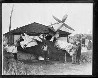 Plane crash: Test pilot Lt. Harold B. Fisher critically injured and William Kraengel of Brooklyn less seriously hurt when plane crashed into garage. Valley Stream, N.Y.