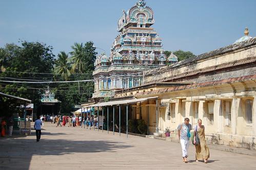 Im Hintergrund ist eine Gruppe von Pilgern, vorne geht ein Paar Touristen an einer Mauer in Sri Rangam