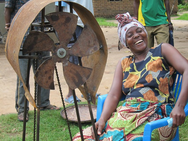 A woman laughs as she sits in front of a machine with a fan in it.