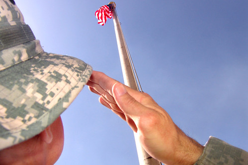 Man in camo hat saluting American flag.