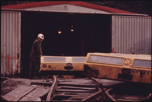 DOCUMERICA: The General Mine Foreman at One of the Tennessee Consolidated Coal Company Mines near Jasper and Chattanooga Stands beside the Shuttle Cars Used to Transport the Miners to Work. They Lay Down on the Cars to Clear the Three Foot High Ceilings During Their Two Mile Trip. It Is a Progressive Non-Union Mine That Sells Most of Its Metallurgical (High Grade) Coal to Japan. August, 1974 by Jack Corn.