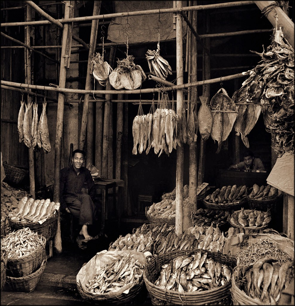 Seated Man Amid Baskets Of Fish & Hanging Dried Fish, Eastern Districts, Hong Kong Island [c1946] Hedda Morrison [RESTORED]
