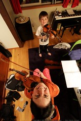 mother & son practice violin in a very cluttered din…