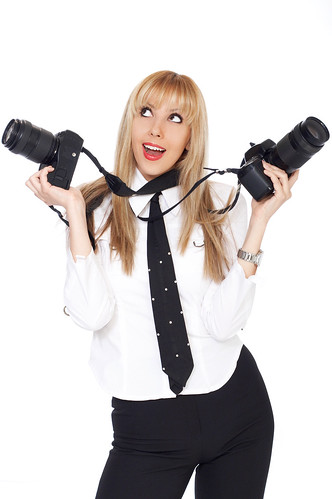 Blond girl holding two cameras