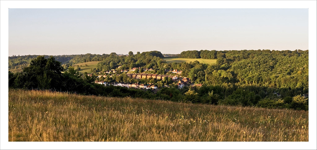 Kenley from Riddlesdown Panorama 4b View from Riddlesdown looking SW towards Kenley. The fields and woods of Kenley Common surround the houses on Hilltop Road and below that Beverley Road. New Barn Lane can be seen as it disappears into the woods and appears again as the footpath across the field leading to Kenley Airfield. The new houses on the far side of the airfield can be seen in the clearing in the trees top centre of the picture.