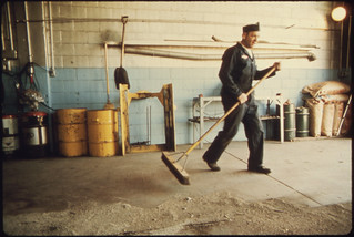 """Wallace """"Whitey"""" Wolf, a Mechanic for the City Sweeps Out the Repair Garage ..., 10/1974"""