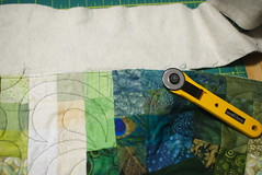 Carefully slice the quilt free of the excess batting and backing, then it's time to make up long strips of fabric to bind off the raw edges.