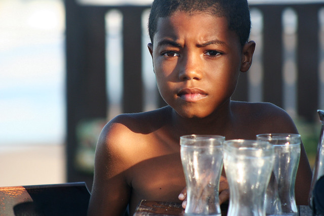 A boy looking through glass in Brazil.