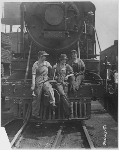 Busch [Bush] Terminal. Women Laborers Seated on Front of Engine in Railroad Yard