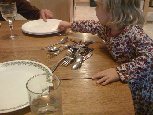 a child sets the dinner table