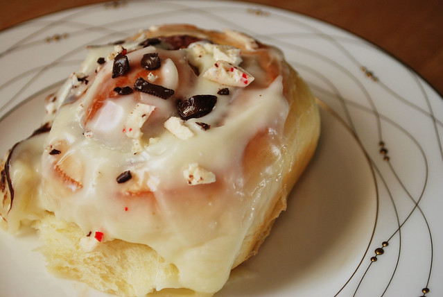 Peppermint Bark Buns - sweet rolls stuffed with chocolate, topped with white chocolate cream cheese frosting, and sprinkled with peppermint bark. Perfect Christmas breakfast!