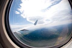 driving(0.0), porthole(0.0), reflection(0.0), window(1.0), cloud(1.0), wing(1.0), vehicle(1.0), sunlight(1.0), fisheye lens(1.0), blue(1.0), sky(1.0), flight(1.0),