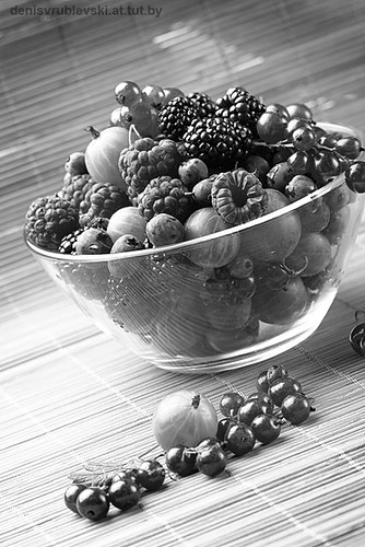 Fruit mix in the glass container, on a table from straw