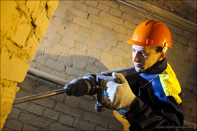 Construction worker hold perforator and drilling brick wall