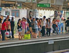People waiting for the next BTS Skytrain at Asok station, Bangkok, Thailand
