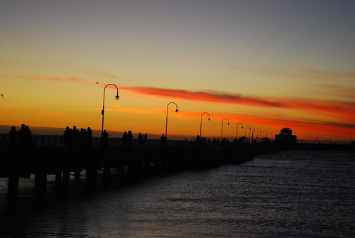 A long pier with lightpoles and a decorative pavilion at the end silhouetted against a sunset sky