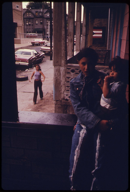 DOCUMERICA: Latin Girl Holding a Child on an Inner City Porch in Paterson New Jersey ... 06/1974 by Danny Lyon.